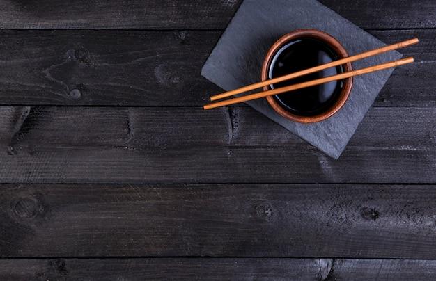 Salsa de soja, palillos en piedra negra, vista superior