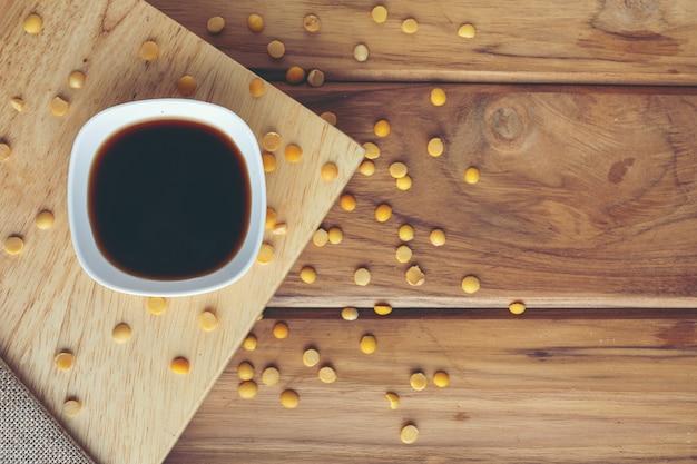 Salsa de soja que se coloca en la madera con semillas de soja crudas esparcidas alrededor.