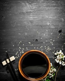 Salsa de soja y ramas de cerezos en flor. sobre un fondo de madera negra.