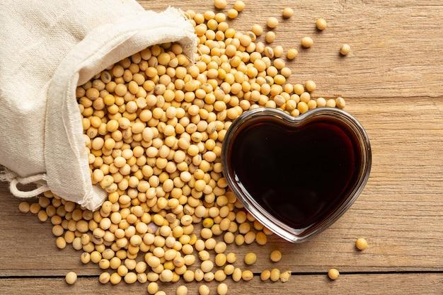 Salsa de soja y soja en el piso de madera salsa de soja concepto de nutrición alimentaria.
