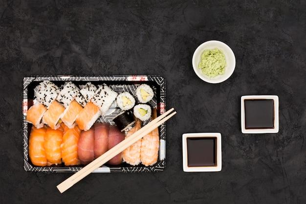 Salsa de soya; wasabi y variedad de rollos de pescado sobre fondo de pizarra