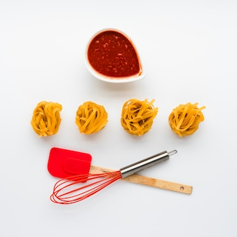 Salsa de tomate y pasta de tallarines crudos con utensilio de cocina aislado sobre fondo blanco.
