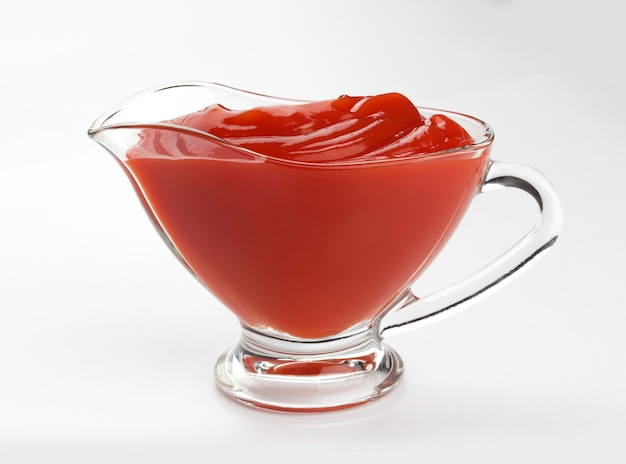 Salsa de tomate en un recipiente de vidrio aislado en blanco