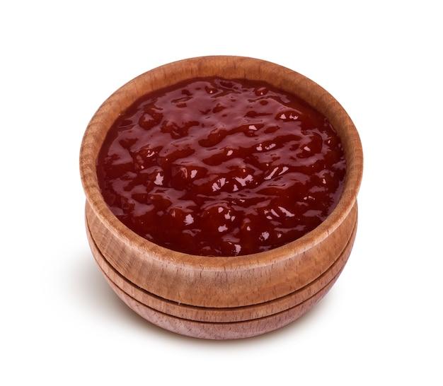 Salsa de tomate en un tazón de madera aislado sobre fondo blanco.