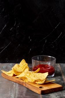 Salsa de tomate en tazón de vidrio y nachos sobre tabla de madera