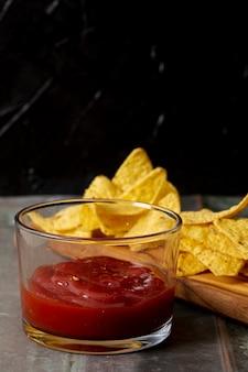 Salsa de tomate en tazón de vidrio y nachos