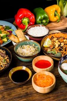 Salsas con comida tradicional tailandesa con pimientos en mesa