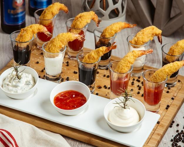 Salsas de langostinos fritos en vista lateral del tablero de madera