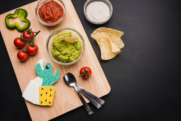 Salsas y verduras en tabla de cortar cerca de nachos.