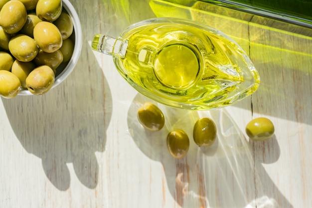 Salsera de vidrio con aceite de oliva virgen extra, aceitunas verdes frescas y botella en mesa de madera.