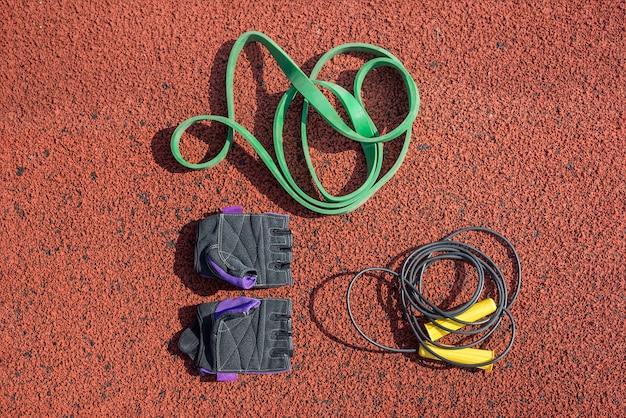 Saltar la comba, guantes deportivos y torniquete para entrenamiento deportivo en la superficie de una cinta de correr.
