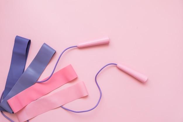 Saltar o saltar la cuerda y la banda elástica de fitness sobre fondo rosa. tendencia de fitness.