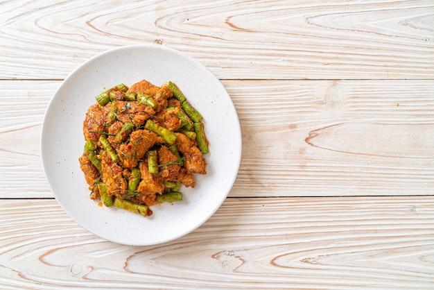 Salteado de cerdo frito y pasta de curry rojo con frijoles picantes - estilo de comida asiática