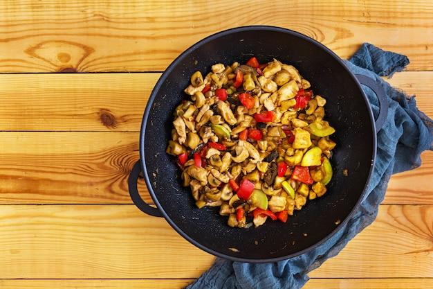 Salteado de pollo, calabacín y pimienta en wok