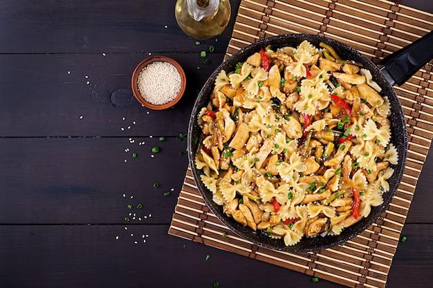 Salteado de pollo, pasta farfalle, calabacín, pimientos y cebolla verde