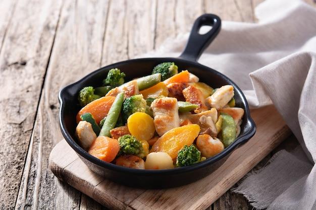 Salteado de pollo con verduras en sartén de hierro sobre mesa de madera