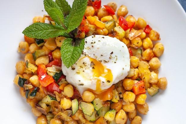 Salteado vegetariano picante casero con garbanzos y dados de pimienta y calabacín con un huevo frito y algo de decoración de menta en un plato blanco. de cerca.