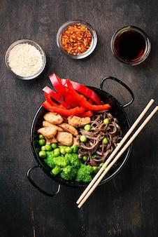 Saltear la soba con carne y verduras.