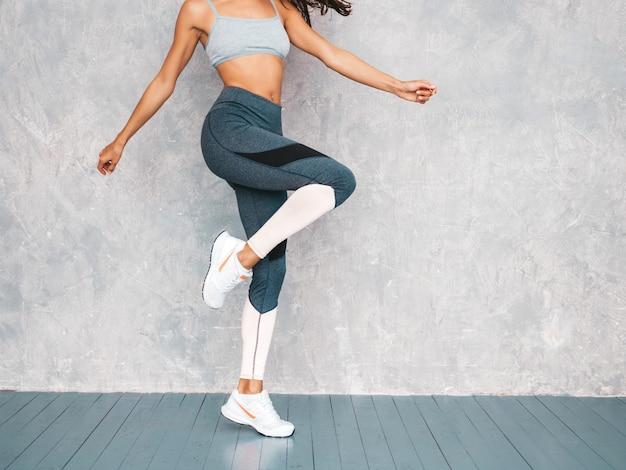 Salto femenino en estudio cerca de la pared gris