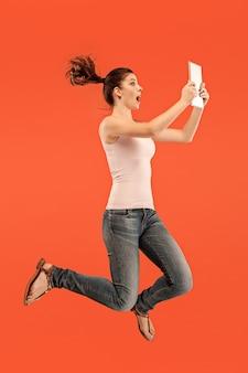 Salto de mujer joven sobre azul con gadget portátil o tableta mientras salta. chica corriendo en movimiento o movimiento
