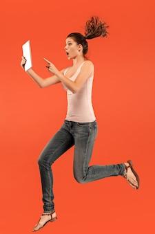 Salto de mujer joven sobre fondo azul de estudio con gadget portátil o tableta mientras salta. chica corriente en movimiento o movimiento.