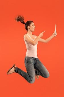 Salto de mujer joven sobre fondo azul de estudio usando un dispositivo portátil o tableta mientras salta. chica corriendo en movimiento o movimiento. concepto de expresiones faciales y emociones humanas. gadget en la vida moderna