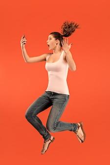 Salto de mujer joven sobre fondo azul de estudio usando un dispositivo portátil o tableta mientras salta. . gadget en la vida moderna