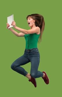 Salto de mujer joven sobre fondo verde de estudio usando un gadget portátil o tableta mientras salta. chica corriendo en movimiento o movimiento. concepto de expresiones faciales y emociones humanas. gadget en la vida moderna