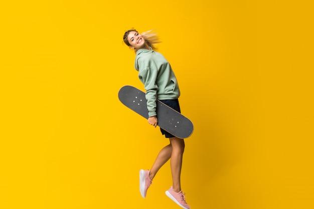 Salto rubio de la muchacha del patinador del adolescente aislado en amarillo