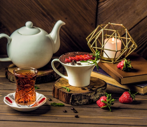 Salto de té con una taza de mousse de chocolate crema
