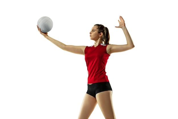 En salto y vuelo. jugador de voleibol femenino joven aislado sobre fondo blanco de estudio. mujer en ropa deportiva y zapatillas de deporte, jugando. concepto de deporte, estilo de vida saludable, movimiento y movimiento.