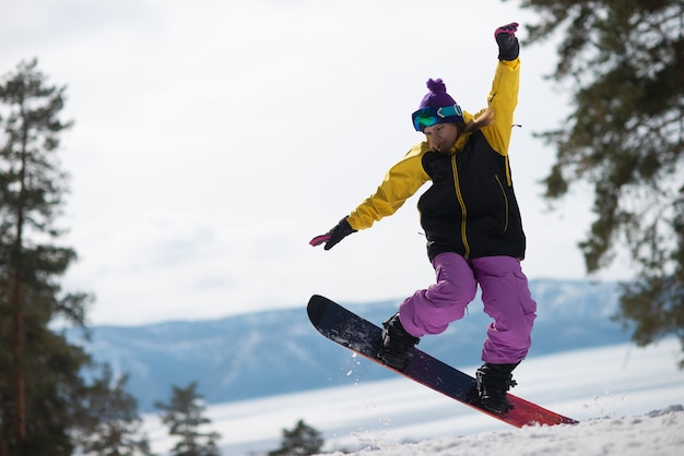 Saltos de mujer montando una tabla de snowboard. deportes de invierno. chica en marcha en una tabla de snowboard