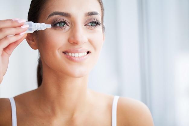 Salud y belleza. cuidado de ojos. hermosa mujer joven con gotas para los ojos. buena visión. chica feliz con mirada fresca