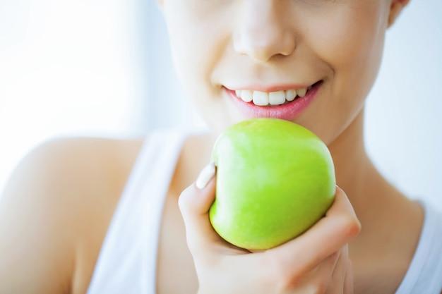 Salud y belleza, hermosa joven con dientes blancos tomados de la mano de manzana verde fresca