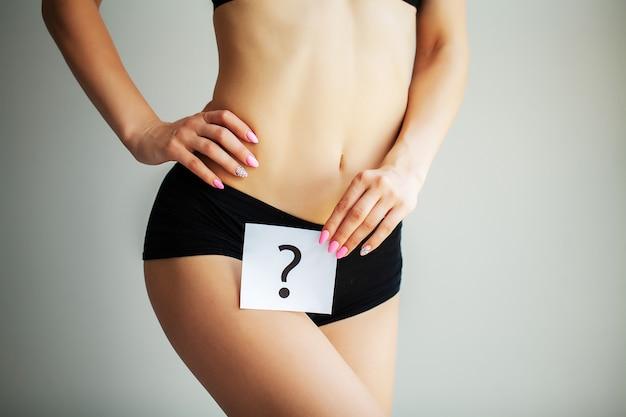 Salud. cuerpo de mujer en ropa interior con tarjeta de pregunta cerca del vientre