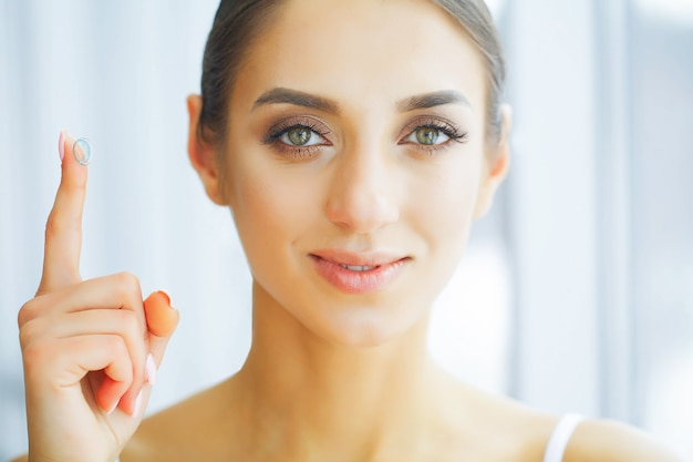 Salud. mujer feliz con lentes de contacto en el dedo. cuidado de ojos.