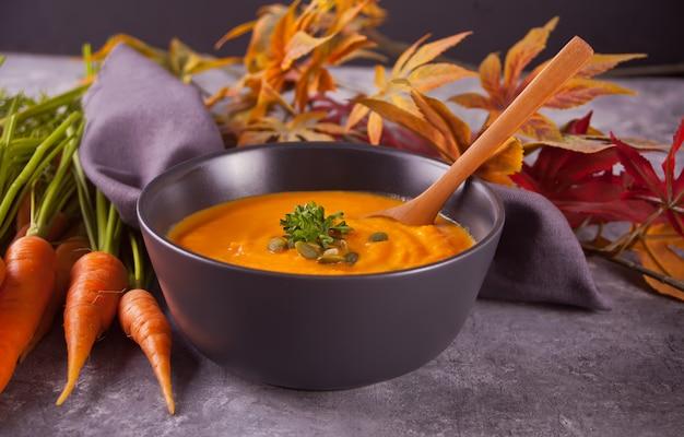 Saludable comer sopa de crema de zanahoria