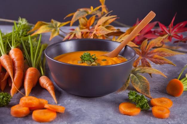 Saludable comer sopa de crema de zanahoria.