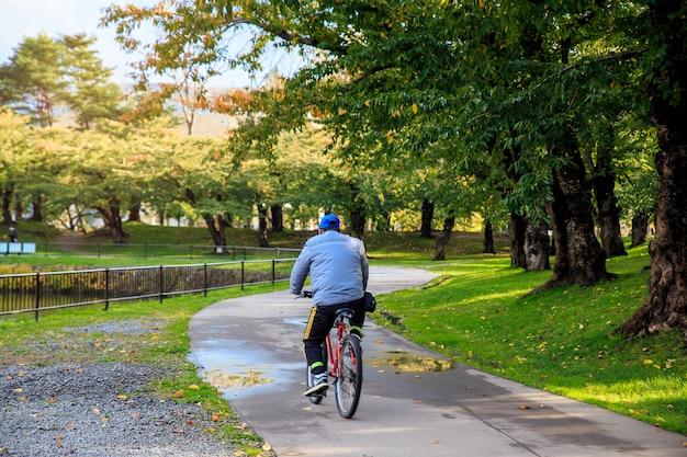 Saludable de deporte asiático hombre ciclismo en el parque. concepto de relajación, concepto de libertad de viaje.