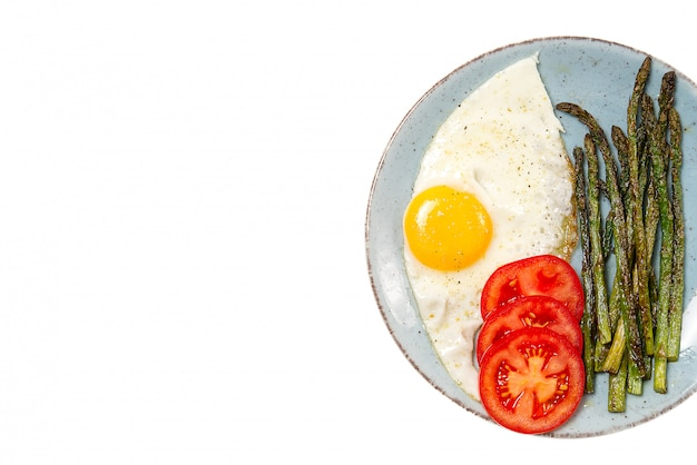 Saludable desayuno casero con espárragos, huevo frito y rúcula.