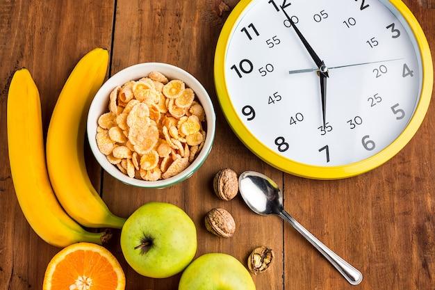 Saludable desayuno casero de muesli, manzanas, frutas frescas y nueces con reloj