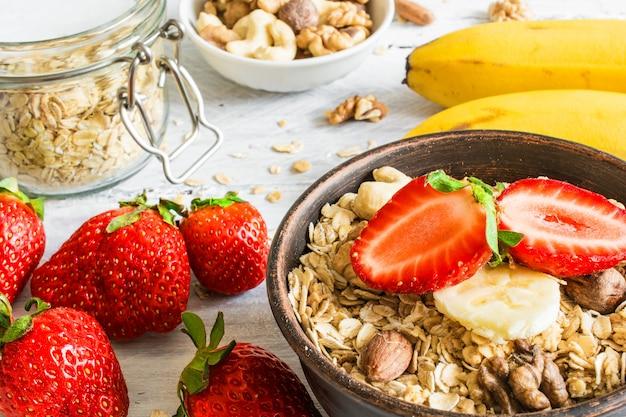 Saludable desayuno muesli de fresa y plátano con avena, granola y nueces en un tazón