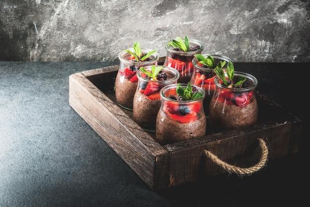 Saludable desayuno vegano. postre. comida alternativa budín con semillas de chía, fresas frescas, moras y menta. sobre un fondo de piedra oscura, en una vieja bandeja de madera. copyspace