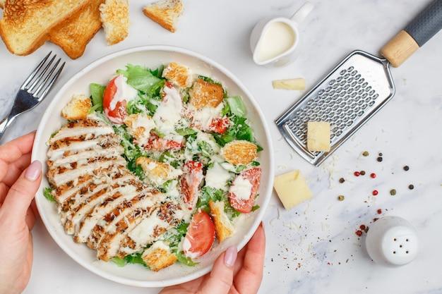 Saludable ensalada césar de pollo a la parrilla con lechuga, queso, tomate, picatostes y salsa gourmet