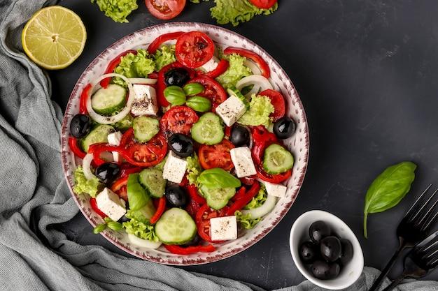 Saludable ensalada griega con aceitunas negras, queso feta y jugo de limón en la oscuridad