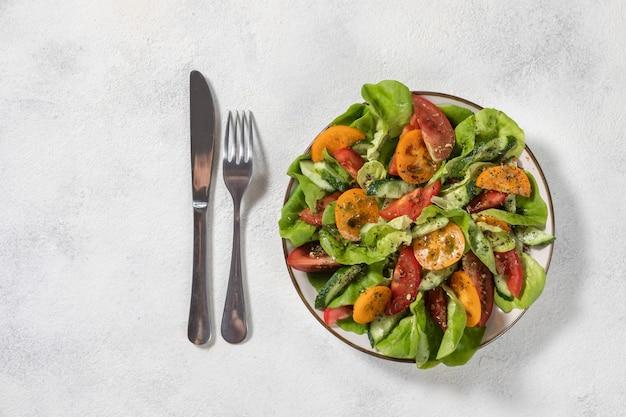 Saludable ensalada de vegetales frescos de tomates, pepinos, cebollas, espinacas, lechuga en un plato. menú de dieta vista desde arriba.
