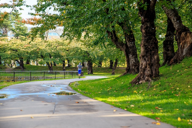 Saludable del hombre asiático del deporte que activa en el parque. concepto de relajación.