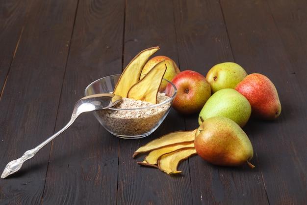 Saludable muesli orgánico o granola con avena, higos secos, pasas, chips de plátano y almendras tostadas y avellanas en un frasco para el desayuno o la merienda
