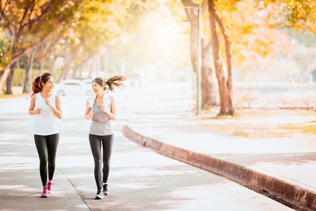 Saludable novia asiática trotar juntos en el parque