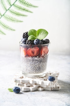 Saludable pudín de chía con fresas, moras, arándanos e higos servidos en un vaso